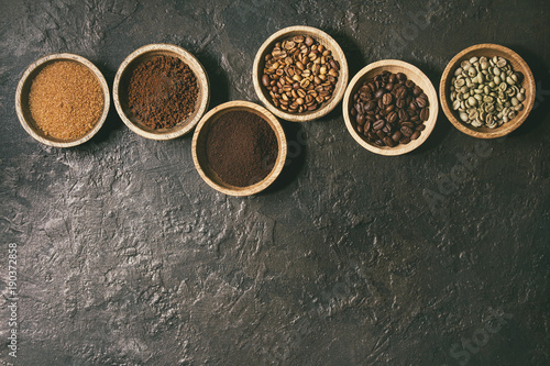 Printed kitchen splashbacks Spices Variety of grounded, instant coffee, different coffee beans, brown sugar in wooden bowls in row over dark texture background. Top view, space. Toned image