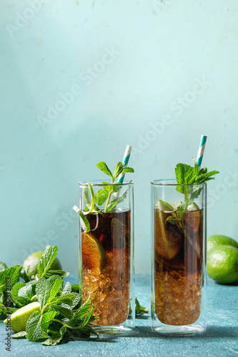 Photo Two Glasses of classic Cuba libre cocktail with lime, mint, crushed ice and cola, served with ingredients above and retro cocktail tubes over turquoise green pin-up style background