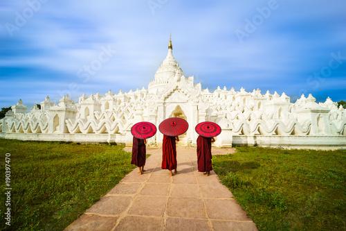 Three Asian young monk holding red umbrellas on the Mya Thein Tan Pagoda at Mingun, Mandalay Myanmar Poster