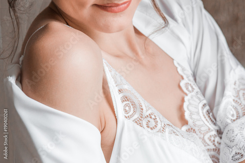 Fotografia  the girl in a white night shirt, shrugged her shoulder, and she shows the tender