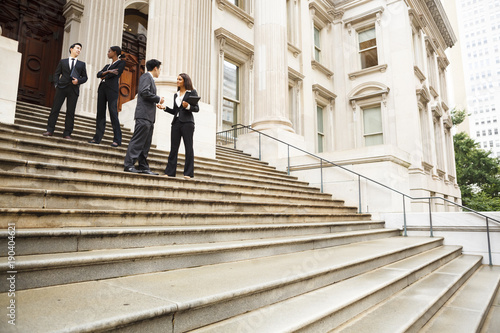Photo Four well dressed professionals in discussion on the exterior steps of a building