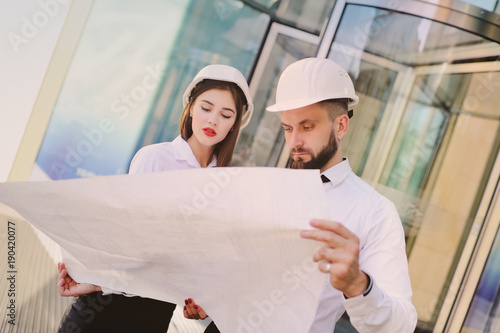 A man with a beard and a woman in business clothes is studying drawings and docu Fototapeta
