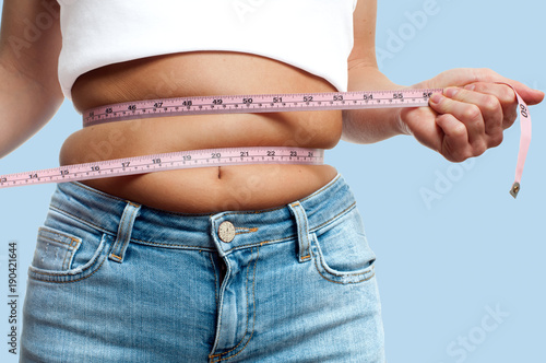 Leinwand Poster Overweight woman with tape measure around waist on pastel background