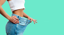Weight Loss. Woman In Oversize Jeans On Green Background