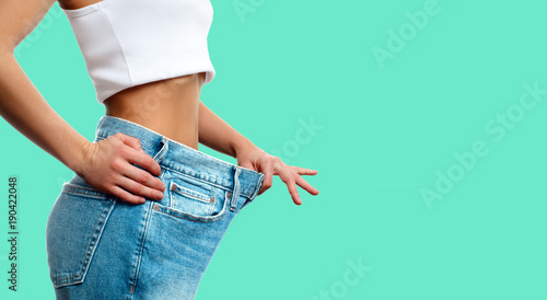 Fotomural Weight loss. Woman in oversize jeans on green background