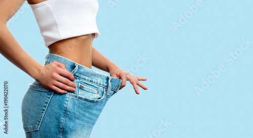 Weight loss. Woman in oversize jeans on pastel blue background Fototapeta