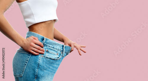 Fotografia  Weight loss. Woman in oversize jeans on pastel pink background