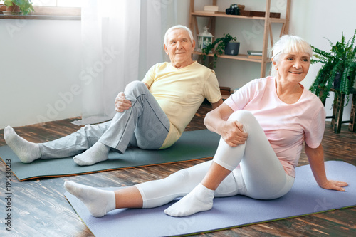 Senior couple doing yoga together at home health care leg stretching ...