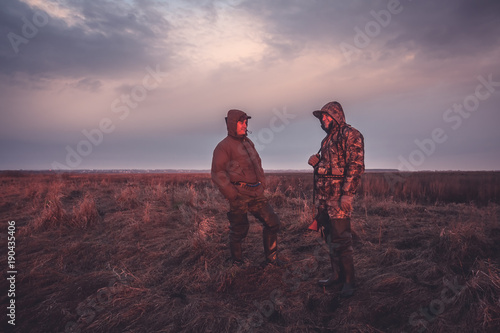 Poster Chasse Hunters during hunting spring season in rural field at sunrise