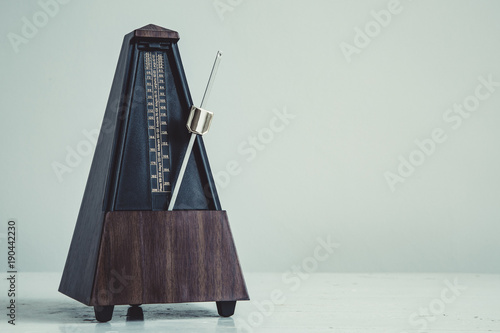 Photo Color shot of a vintage metronome, on gray background.