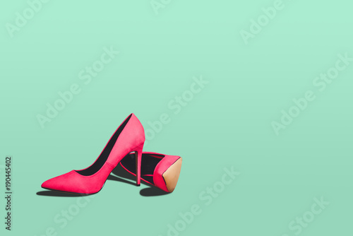 Valokuvatapetti Red high heels isolated on a bright green pastel background