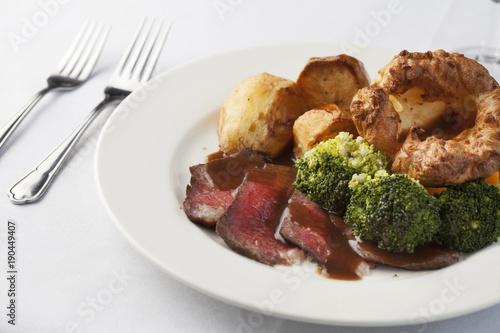Fotografie, Obraz  Traditional British roast dinner of rare beef, yorkshire pudding, roast potatoes and brocolli with gravy