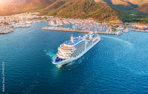 Cruise ship at harbor. Aerial view of beautiful large white ship at sunset. Colorful landscape with boats in marina bay, sea, green forest. Top view from drone of yacht. Luxury cruise. Floating liner