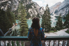 Woman Looking At View While Standing In Balcony Against Mountains And Lake