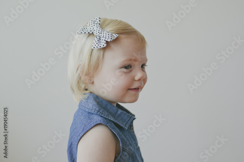 Side view of cute girl wearing bow on her hair against gray background