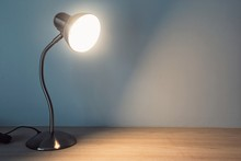 Table Lamp With Light-on On The Wooden Table In Vintage Style.