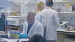 Tilt shot of doctors working in laboratory at hospital seen through glass