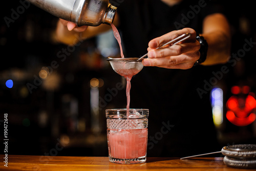 Fotografia  barman poured an alcoholic cocktail from the shaker into a crystal glass