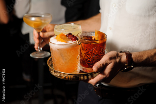 Photo man i is holding a tray with glasses with amber Negroni and yellow sour mix