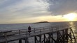 Drone footage of woman standing on pier over sea during sunset
