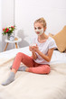 beautiful young woman with white clay facial mask with milkshake in mason jar at home
