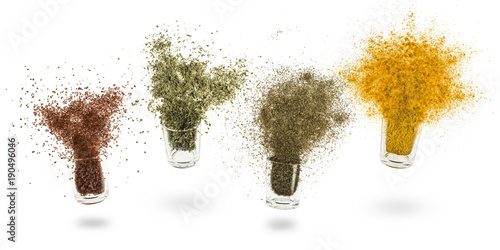 glass jars with various spices flying on white background