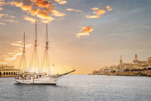 Sunset With A Yacht In Valletta, Capital City Of Malta, Known In Maltese As Il-Belt. Scenic City View From The Bay With A Ship In Front.