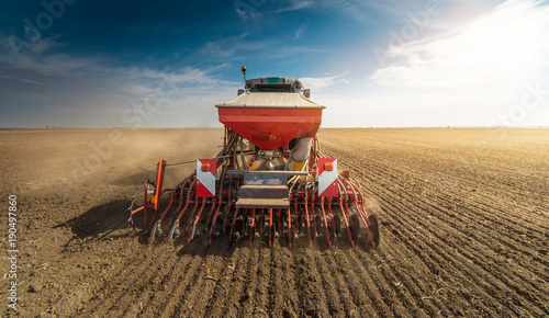 Fotografia Farmer with tractor seeding - sowing crops at agricultural fields