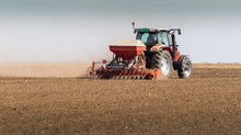 Farmer With Tractor Seeding - ...