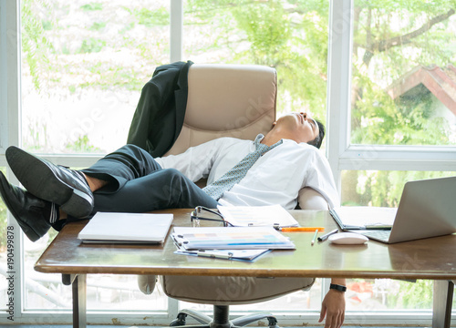 Obraz Tired businessman sleeping in the office with his feet up on the desk - fototapety do salonu