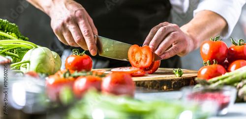 Keuken foto achterwand Kruidenierswinkel Chefkoch in der Küche mit Frischem Gemüse(Tomaten)