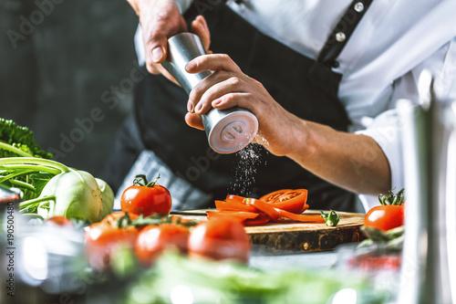 Photo Chefkoch in der Küche mit Frischem Gemüse(Tomaten)