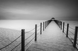 Fototapeta Bridge - Long exposure image of old abandoned fisherman jetty in black and white
