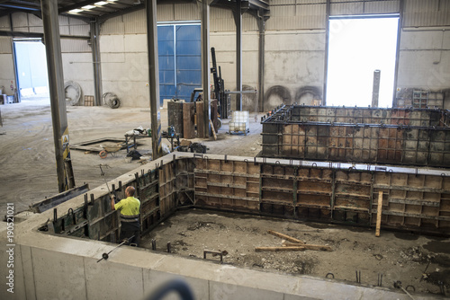 Man adjusting concrete structure in construction factory