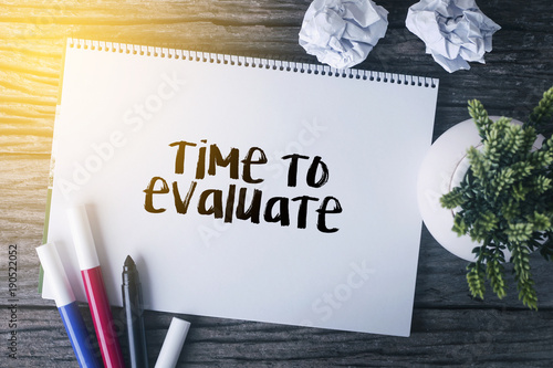 Fotomural Time to evaluate word with Notepad and green plant on wooden background