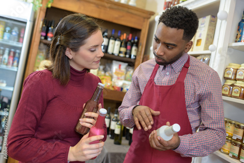 Fotografía salesman in supermarket offering bottle of to woman