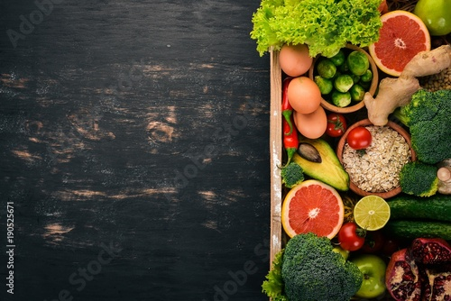 The concept of healthy food. Fresh vegetables, nuts and fruits in a wooden box. On a wooden background. Top view. Copy space. © Yaruniv-Studio