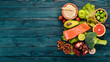 Leinwandbild Motiv Healthy food. Fish salmon, avocado, broccoli, fresh vegetables, nuts and fruits. On a wooden background. Top view. Copy space.