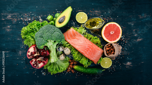 Healthy food. Fish salmon, avocado, broccoli, fresh vegetables, nuts and fruits. On a black background. Top view. Copy space.