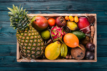 Tropical Fruit In A Wooden Box. Papaya, Dragon Fruit, Rambutan, Tamarind, Cactus Fruit, Avocado, Granadilla, Carambola, Kumquat, Mango, Mangosteen, Passionfruit, Coconut.