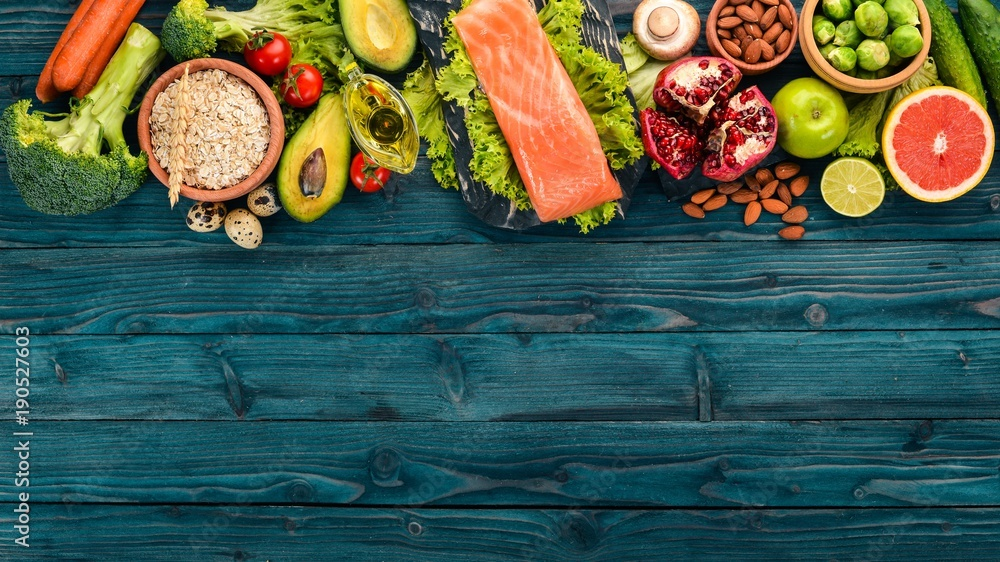 Fototapety, obrazy: Healthy food. Fish salmon, avocado, broccoli, fresh vegetables, nuts and fruits. On a wooden background. Top view. Copy space.