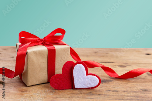 Valentine Gift Box With Red Hearts On Rustic Wooden Table Against