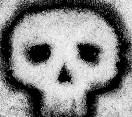 Crystals of sugar on a black background in the form of a skull. Danger of diabetes.
