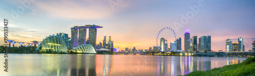 Fotobehang Singapore Business city district of Singapore Skyline. At marina bay sand and the garden by the bay on sunset with modern tower building with lighting and colorful of sky cloud.