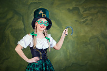 A Girl In A St. Patrick Costume With A Horseshoe In Hands Smiles On A Green Background. St. Patrick's Day.