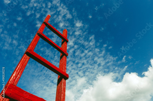 Fototapeta Red Staircase Rests Against Blue Sky