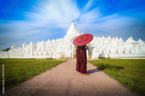 Asian young monk holding red umbrellas on blue sky in the Mya Thein Tan Pagoda at Mingun, Mandalay Myanmar Poster