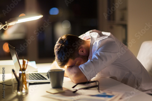 tired businessman lying on table at night office Obraz na płótnie