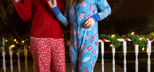 Two Young Caucasian Woman Dance Outside In Their Adult One Piece Pajamas At Night With Christmas Decoratoins