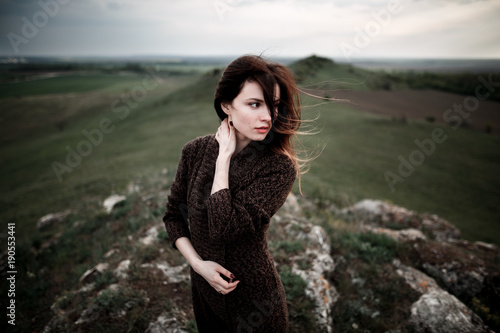 Poster Kaki Portrait of beautiful young woman standing on the cliff, watching the last light. Hair blowing in the wind.Girl admiring mountain landscape. A woman standing alone in sunset scene